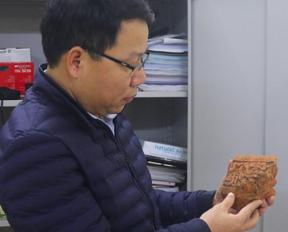 Ông Trần Phi Công, cán bộ Bảo tàng tỉnh Hà Tĩnh bên hiện vật vừa được phát hiện