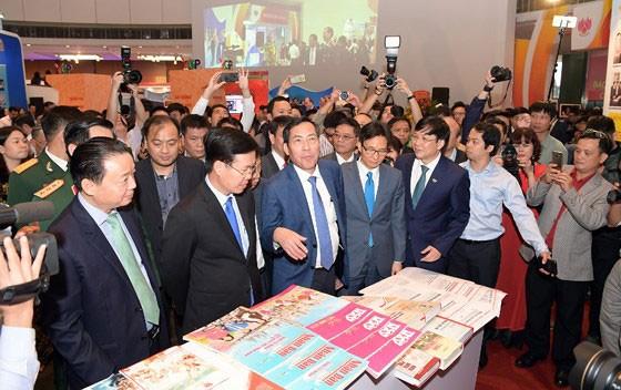 Các đồng chí lãnh đạo Đảng, Nhà nước và các bộ ngành tham quan một gian trưng bày tại Hội Báo toàn quốc 2018. Ảnh: TRẦN BÌNH