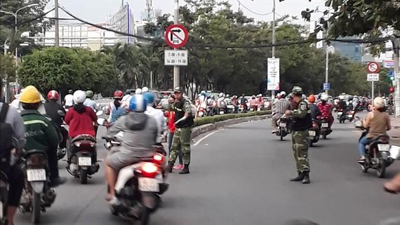 Các nhân viên bảo vệ của cao ốc gần cầu Sài Gòn ra đường phân luồng cho xe máy lưu thông qua làn đường dành cho ô tô  Ảnh: ĐOÀN HIỆP