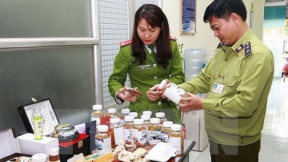 Lực lượng chức năng kiểm tra các sản phẩm thực phẩm chức năng nhập lậu. Ảnh: TTXVN
