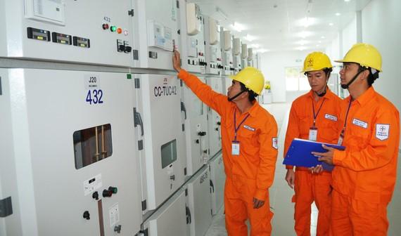 Công nhân EVNSPC vận hành trạm biến áp 110kV  cung ứng điện đến người dân. Ảnh: CAO THĂNG