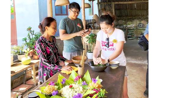 Khách thích thú trải nghiệm, tìm hiểu các loại ẩm thực  được trang trí bằng lá tại nhà dân ở tỉnh Trà Vinh