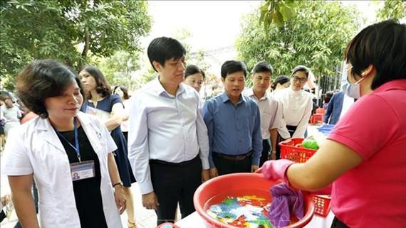 Các đại biểu tham quan thực hành rửa tay bằng xà phòng cho trẻ, vệ sinh đồ dùng giảng dạy và đồ chơi của trẻ tại trường mầm non Dịch Vọng Hậu, quận Cầu Giấy) ngay sau lễ triển khai chiến dịch phòng chống dịch bệnh