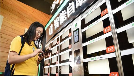 Người dân mua đồ ăn nhanh bằng dịch vụ thanh toán qua điện thoại ở Trùng Khánh, Trung Quốc ngày 23-8-2018. Ảnh: THX