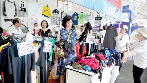Khách hàng chọn mua quần áo ở một hội chợ tổ chức tại Nhà thi đấu Phú Thọ, TPHCM. Ảnh: THÀNH TRÍ