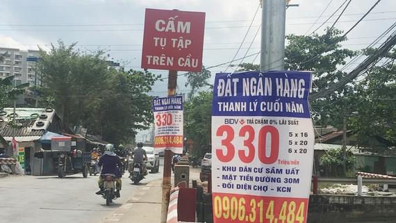Bảng quảng cáo ngân hàng thanh lý nền đất giá rẻ treo dày trên đường Đỗ Xuân Hợp (quận 9, TPHCM)