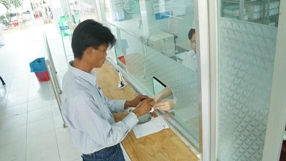 Bệnh nhân nhận thuốc ARV thông qua Quỹ BHYT chi trả tại Trung tâm Y tế huyện Bình Chánh vào sáng 8-3
