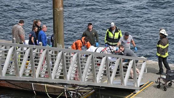 Lực lượng cứu hộ đang chuyển một hành khách bị thương đến xe cứu thương tại bến cảng George Inlet Lodge ở Ketchikan, Alaska. Ảnh: AP