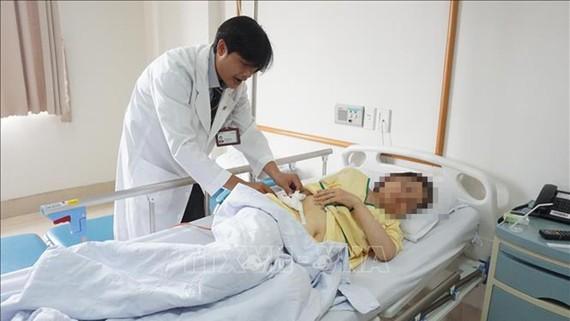 Bệnh nhân Nguyễn Thị Như T được bác sĩ kiểm tra tình hình sức khỏe trước khi xuất viện