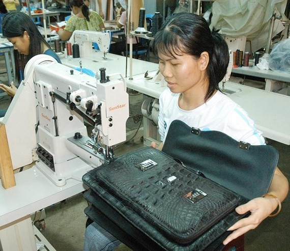 Workers make leather bags for export at a company in District 12 in Ho Chi Minh City. (Photo: SGGP)