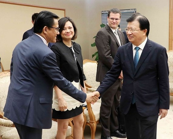 Deputy Prime Minister Trinh Dinh Dung (R) receives representatives from French enterprises (Source: VNA)