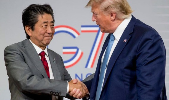 U.S President Donald Trump, right, and Japanese Prime Minister Shinzo Abe shake hands following a news conference at the Group of Seven summit in France.   © AP
