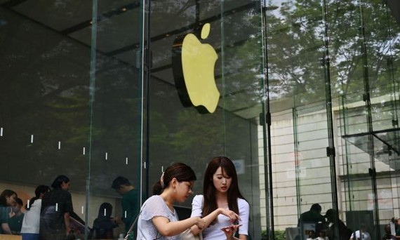 Women use their smartphones in front of an Apple store in Tokyo's Omotesando district on June 4, 2019. (CHARLY TRIBALLEAU/AFP/Getty Images)