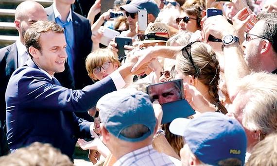 Tổng thống Pháp Emmanuel Macron (trái) gặp gỡ cử tri sau khi bỏ phiếu