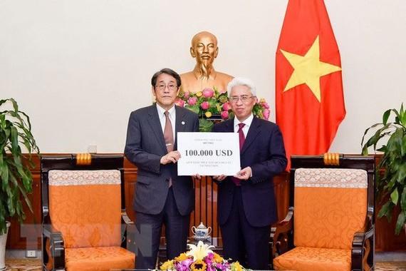 Đại diện Bộ Ngoại giao đã trao cho Đại sứ Nhật Bản tại Việt Nam khoản hỗ trợ. (Ảnh: TTXVN )
