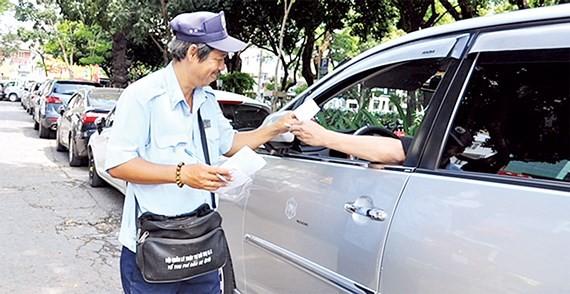 Thu phí đậu ô tô ở lòng đường tại quận 1, TPHCM. Ảnh: KIỀU PHONG