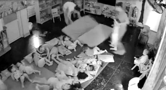 Hai nhân viên tại cơ sở mầm non tư thục Đồ Rê Mí xách tay trẻ nhỏ bắt nằm xuống chiếu. Ảnh cắt từ clip