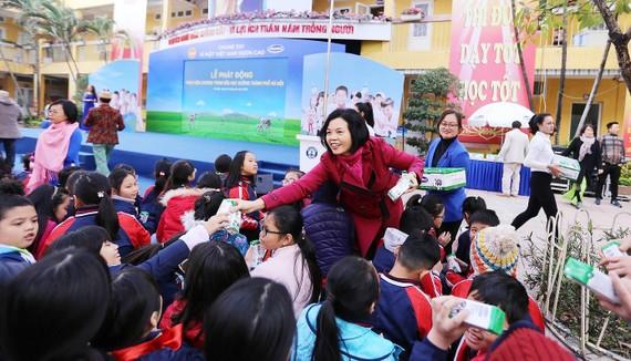 Bà Bùi Thị Hương, Giám đốc Điều hành Vinamilk trao sữa cho các em học sinh tại Lễ phát động thực hiện chương trình Sữa học đường tại thủ đô Hà Nội, đầu tháng 1-2019. Ảnh: VNM