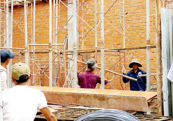 Công nhân xây dựng làm việc dưới giàn giáo nhưng không được trang bị đồ bảo hộ. Ảnh: THÁI PHƯƠNG