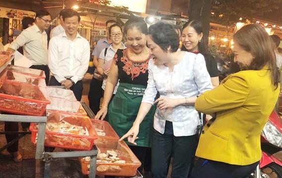 Bà Phạm Khánh Phong Lan, Trưởng ban Quản lý ATTP TPHCM tham quan cơ sở kinh doanh thức ăn đường phố tại phố ẩm thực Vĩnh Khánh.