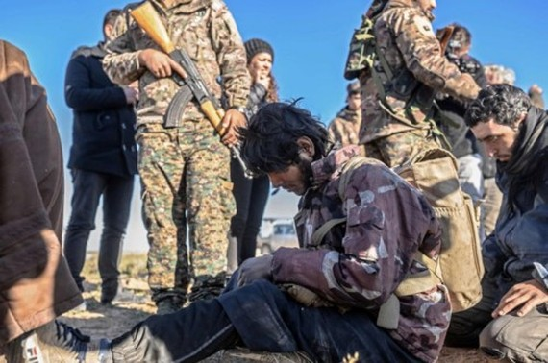 Những tay súng nghi thuộc IS bị SDF bắt giữ. Ảnh: Guardian