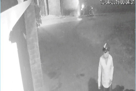 Người bịt mặt dùng ổ khóa, khóa cổng nhà riêng của phóng viên Đ.T. Ảnh: Thanh Niên