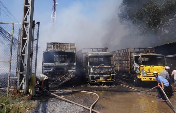 Vụ cháy làm 3 xe tải và nhiều tài sản khác bị thiêu rụi. Ảnh: TTXVN
