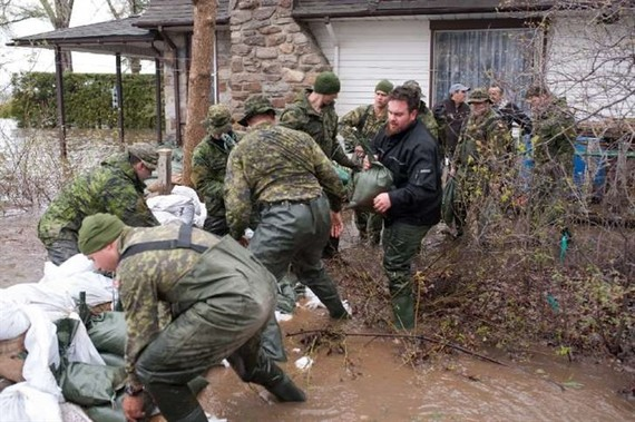 Soldiers help residents of Pierrefonds after heavy flooding caused by unrelenting rain. – AFP/VNA Photo