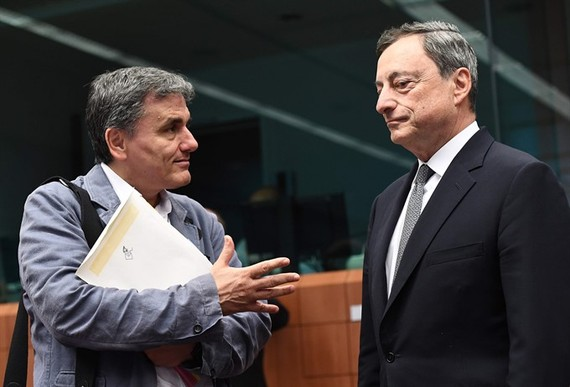 Greece's Finance Minister Euclid Tsakalotos (left) speaks with European Central Bank President Mario Draghi during a Eurogroup finance ministers meeting on Monday at the European Council in Brussels. - AFP/VNA