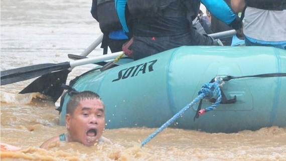 A man clings onto the rope of a rescue boat as residents are evacuated from their homes due to heavy flooding in Cagayan de Oro city in the Philippines CREDIT: FROILAN GALLARDO/REUTERS