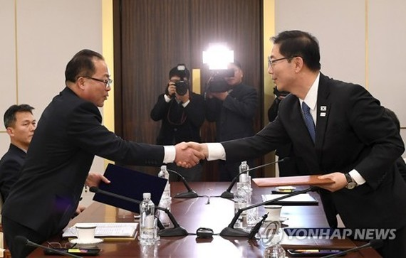 South Korean and North Korean chief delegates shake hands after agreeing at talks on Jan. 17, 2018, to march together under a unified flag at the opening ceremony of the PyeongChang Olympics. (Yonhap)