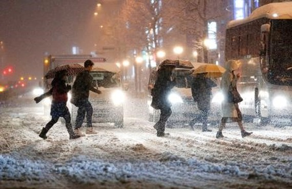 Pedestrians cross the street in the snow, in front of JR Yotsuya Station, in Tokyo, on Monday. - KYODO