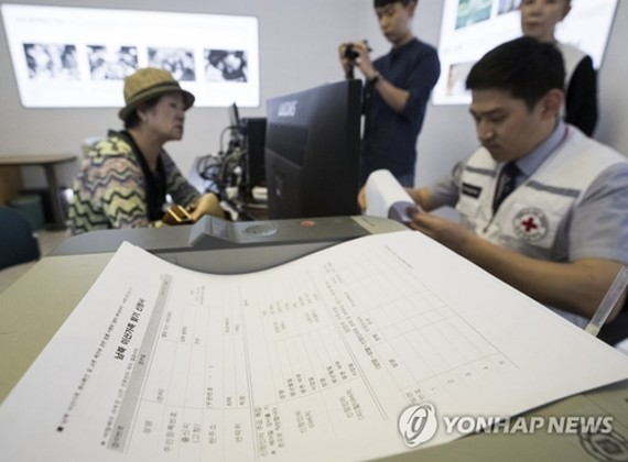 A South Korean woman talks with a Red Cross official to see if she can meet with her family in North Korea in this undated file photo. (Yonhap)