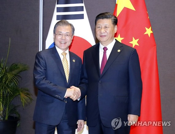 South Korean President Moon Jae-in (L) shakes hands with Chinese President Xi Jinping before their talks in Papua New Guinea on the sidelines of the Asia Pacific Economic Cooperation (APEC) forum on Nov. 17, 2018. (Yonhap)
