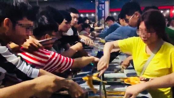 Giới trẻ tranh giành nhau gắp thức ăn tại tiệc buffet miễn phí ở Cần Thơ (ảnh cắt từ clip)
