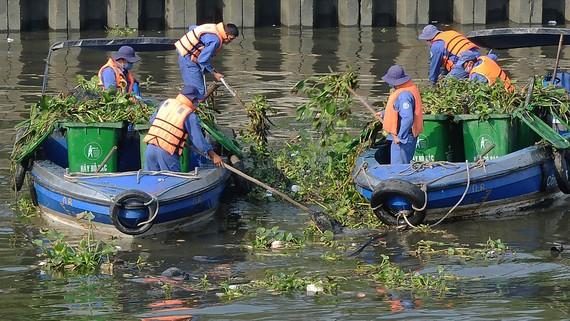 Vớt rác làm sạch môi trường không để dòng chảy bị tắc nghẽn. Ảnh: Thành Trí