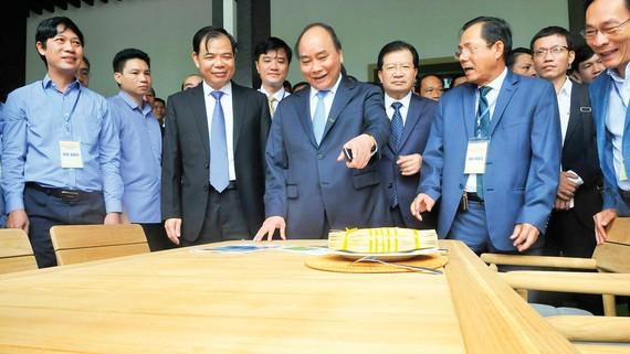 Thủ tướng Nguyễn Xuân Phúc xem sản phẩm đồ gỗ sản xuất trong nước trưng bày tại Hội nghị về định hướng, giải pháp phát triển nhanh, bền vững ngành công nghiệp chế biến gỗ và lâm sản xuất khẩu ngày 8-8. Ảnh: CAO THĂNG