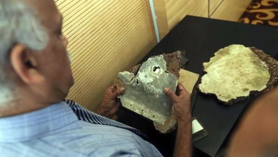 Một quan chức Malaysia kiểm tra các mảnh vỡ được cho là từ máy bay MH370 trong cuộc họp báo tại trụ sở Bộ Giao thông Malaysia ở Putrajaya ngày 30-11-2018. Ảnh: EPA-EFE