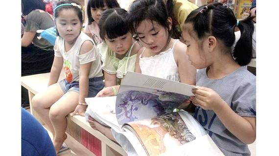 Bạn đọc nhí thích thú cuốn sách Thiện và Ác và Cổ tích - sách Artbook do NXB Kim Đồng ấn hành