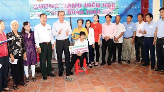 Ông Lưu Hoàng Tân - Chủ tịch, Giám đốc Công ty TNHH MTV Xổ số kiến thiết Đồng Tháp (thứ năm từ trái sang) trao học bổng cho em Nguyễn Thị Anh Đào