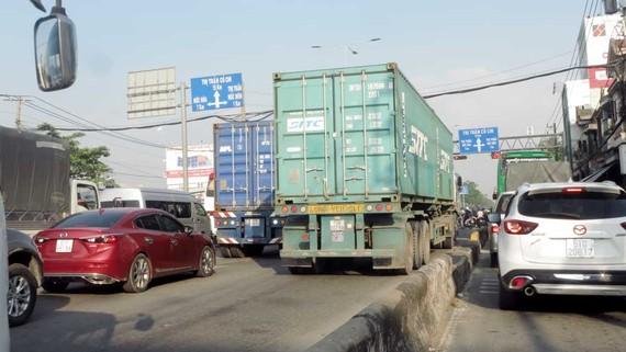 Lưu lượng ô tô lưu thông trên quốc lộ 22 ngày một quá tải, tạo áp lực căng thẳng cho lái xe tải hạng nặng - nhất là xe container. Ảnh: VĂN PHONG