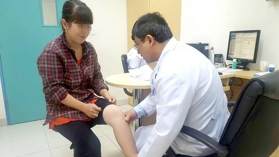 Kỹ thuật viên đang tập vật lý trị liệu phục hồi chức năng cho người bệnh