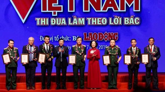 Đồng chí Trương Thị Mai, Ủy viên Bộ Chính trị, Bí thư Trung ương Đảng, Trưởng ban Dân vận Trung ương trao biểu trưng vinh danh các tập thể có thành tích xuất sắc. Ảnh: TTXVN