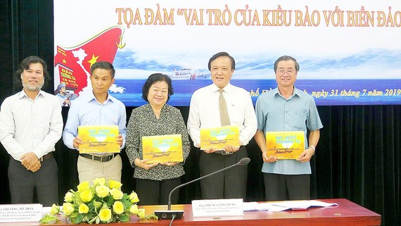 Ông Hoàng Chí Hùng (bìa trái), Chủ nhiệm CLB Ảnh báo chí  Hội Nhà báo TPHCM, tặng các đại biểu sách ảnh về biển đảo