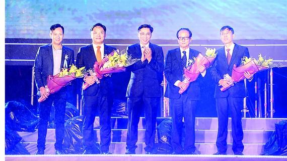 Ông Lê Đức Vinh, Chủ tịch UBND tỉnh Khánh Hòa (ở giữa) tặng hoa cảm ơn cho các nhà tài trợ. Từ bên trái qua: ông Hồ Xuân Dũng - Tổng Giám đốc Công ty Cổ phần Dấu Ấn Việt Nam; ông Truong Vincent - Chủ tịch, Tổng Giám đốc Sunny World Corp; ông Cheung Fung
