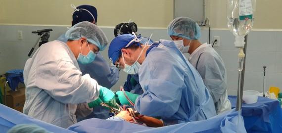 Các sác sĩ đoàn phẫu thuật từ thiện Operation Walk Chicago và BV Quân y 175 tiến hành phẫu thuật thay khớp cho bệnh nhân. Ảnh: BV cung cấp