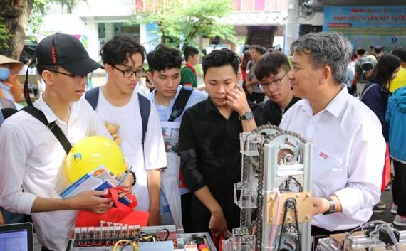 Các em học sinh thích thú với mô hình rô bốt của khoa Điện tử - Tự động HIU trong Ngày hội tư vấn xét tuyển sáng 21-7 tại Đại học Bách Khoa