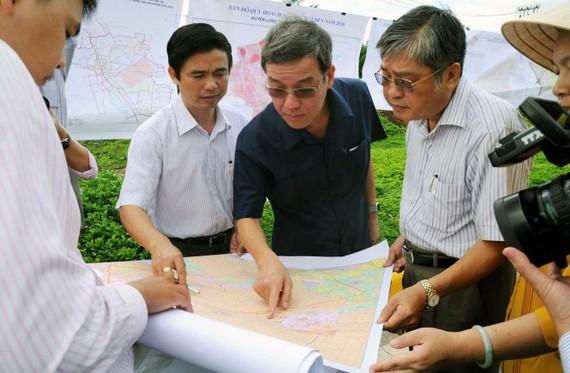 Chủ tịch UBND tỉnh Đồng Nai Đinh Quốc Thái (giữa) xem bản đồ quy hoạch sử dụng đất tại khu vực quy hoạch sân bay Long Thành (ảnh chụp tháng 7-2016) - Ảnh: A Lộc