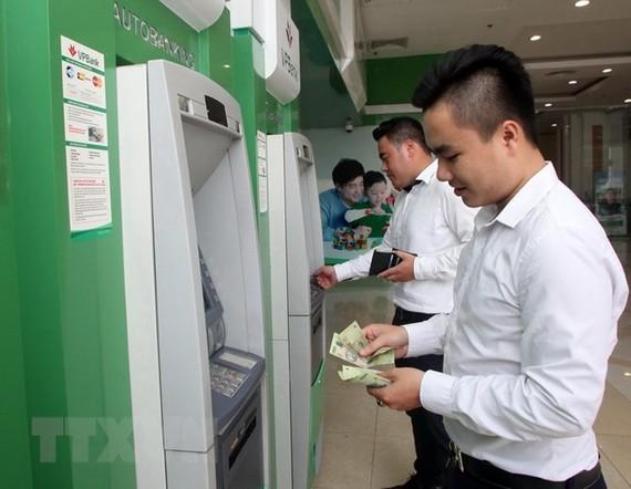 Khách hàng giao dịch tại điểm thanh toán thẻ ATM Ngân hàng VPBank. (Ảnh: Trần Việt/TTXVN)