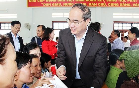 Bí thư Thành ủy TPHCM Nguyễn Thiện Nhân trao quà cho 100 người nghèo, nạn nhân da cam tại xã Nhơn Phong, Bình Định trong dịp đón Tết Mậu Tuất 2018. Ảnh: NGỌC OAI